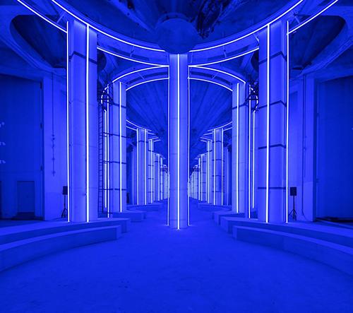 Studio AMO navrhlo pro pánskou přehlídku značky Prada futuristický neonový prostor se sily